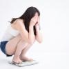 体重計に乗る女性の画像です